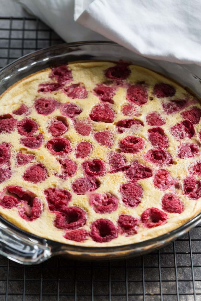 Raspberry clafoutis in a glass pie pan on a rack