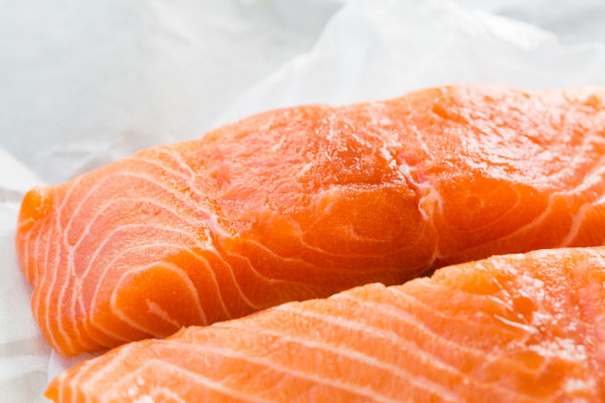 Raw salmon fillets on white paper