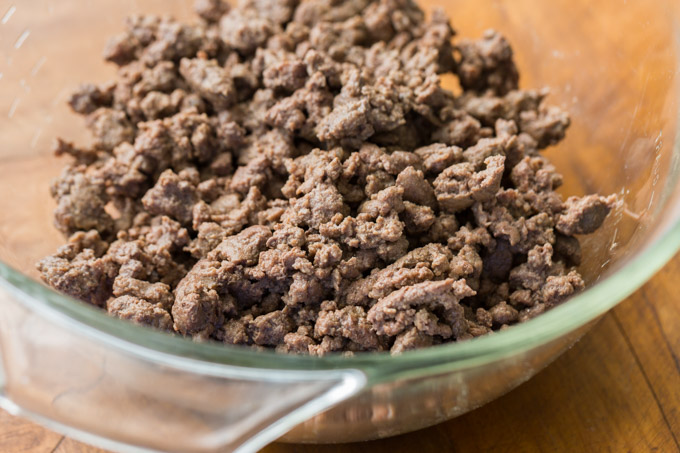 Cooked ground beef in a glass mixing bowl