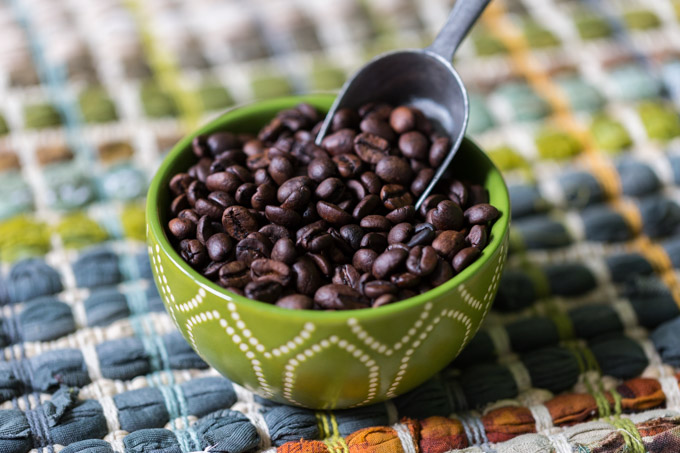 Shade grown roasted coffee beans in a green bowl