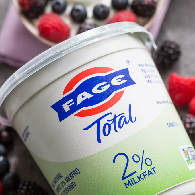 Large container of FAGE Total 2% Greek Yogurt with berries in the background