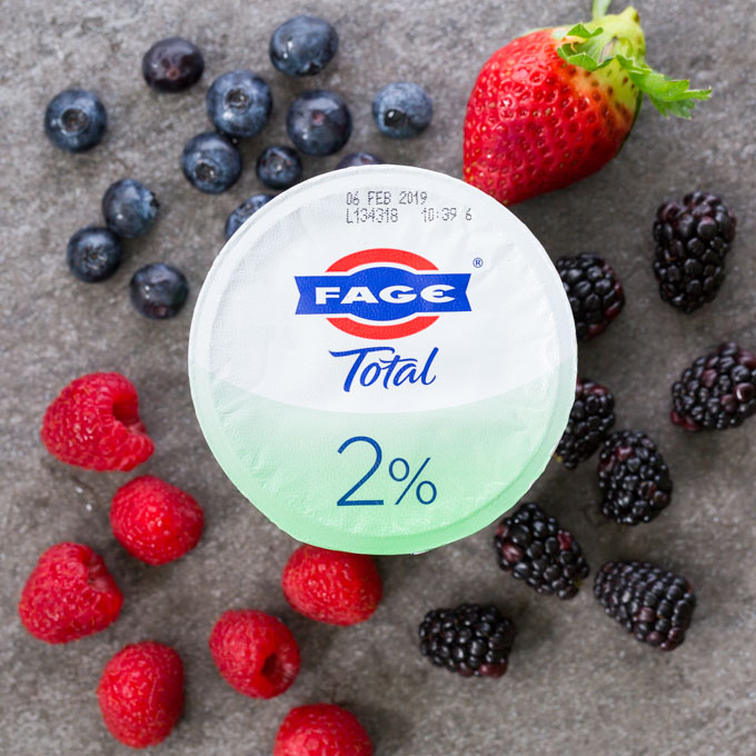 Small FAGE yogurt cup surrounded by blueberries, raspberries, blackberries, and a strawberry