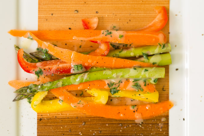 Raw asparagus, bell pepper slices, and carrot slices ready to cook in a cedar wrap