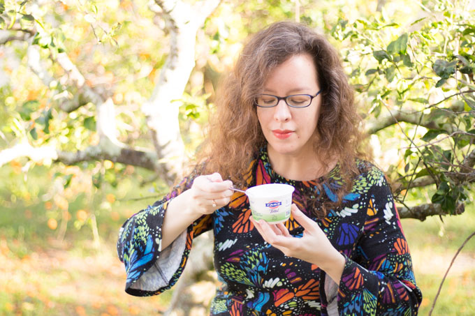 Woman eating FAGE Total Greek Yogurt with a spoon outside