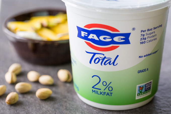 Container of FAGE Total Greek Yogurt next to pistachios with a yogurt bowl