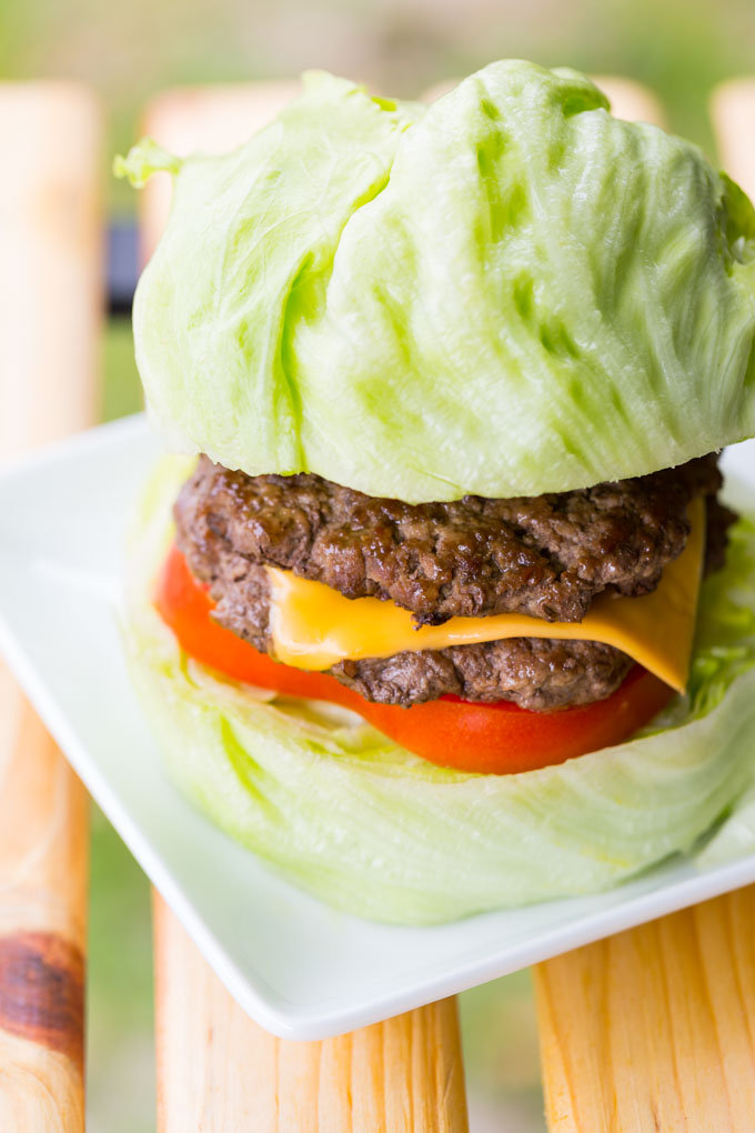 Grilled bison burger patties on a lettuce bun with tomato and American cheese