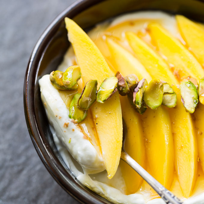 Mango Pistachio Cardamom Yogurt Bowl in a dark brown bowl with vintage spoon