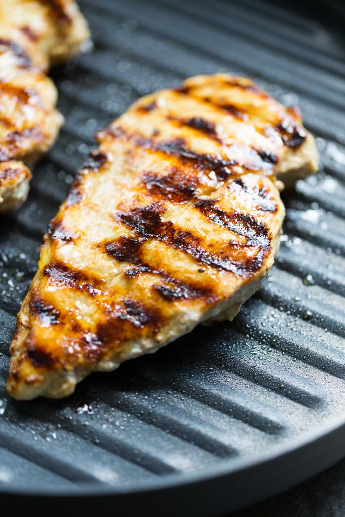 Yogurt marinated chicken breast cooking in a nonstick grill pan with grill marks