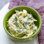 Hot spinach artichoke dip in a green bowl on a white plate with blue corn tortilla chips