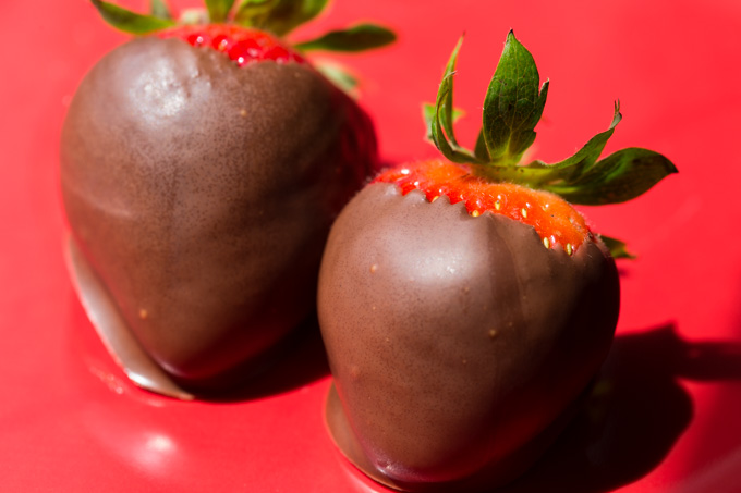Two chocolate covered strawberries on a red plate
