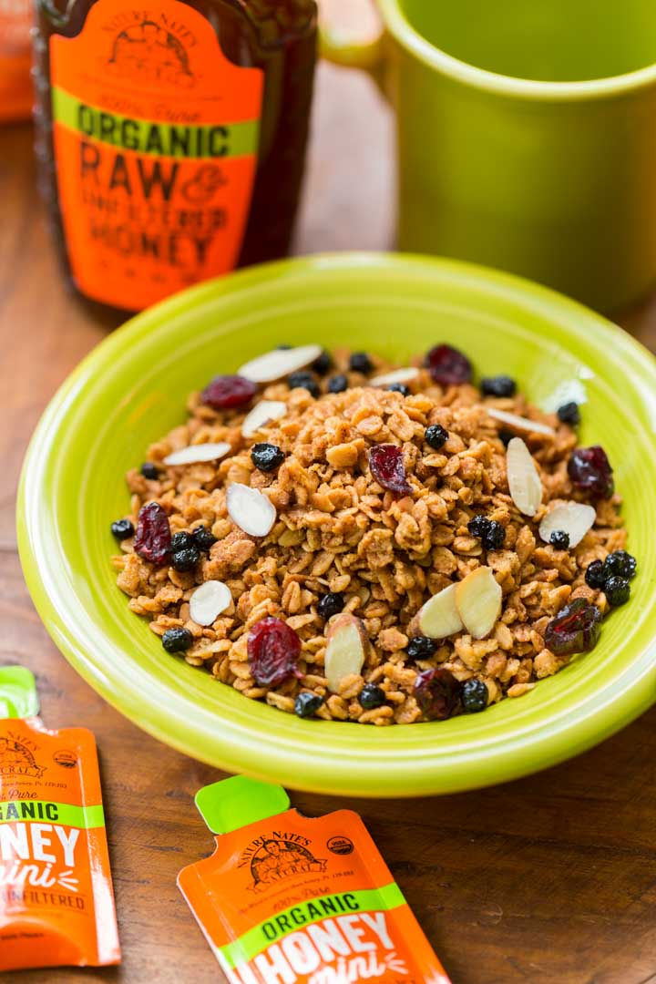 Honey granola in a green bowl next to a bottle of honey and a green mug