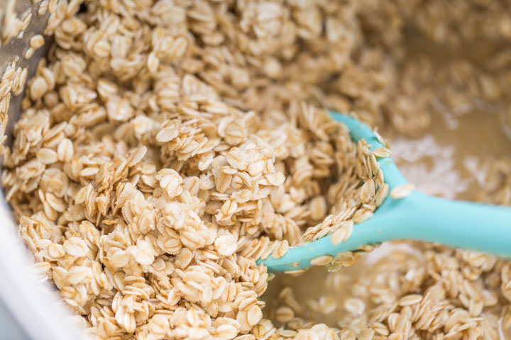 Raw oats mixed with honey, buttermilk, and other ingredients for honey granola recipe in a bowl