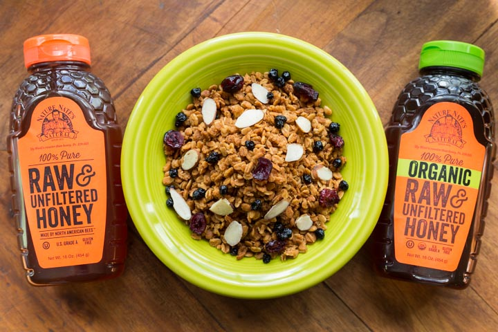 Honey granola next to two bottles of honey on a wooden table