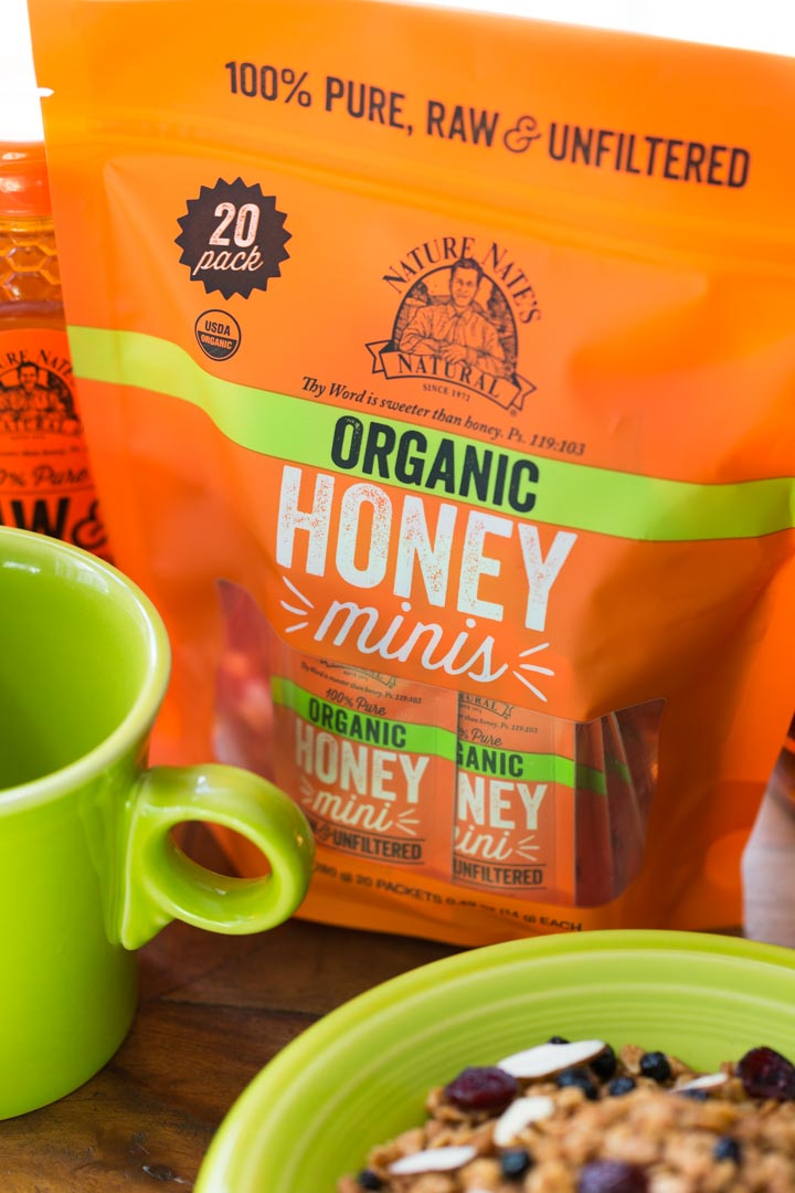 Package of Nature Nate's honey packets next to breakfast cereal and a mug