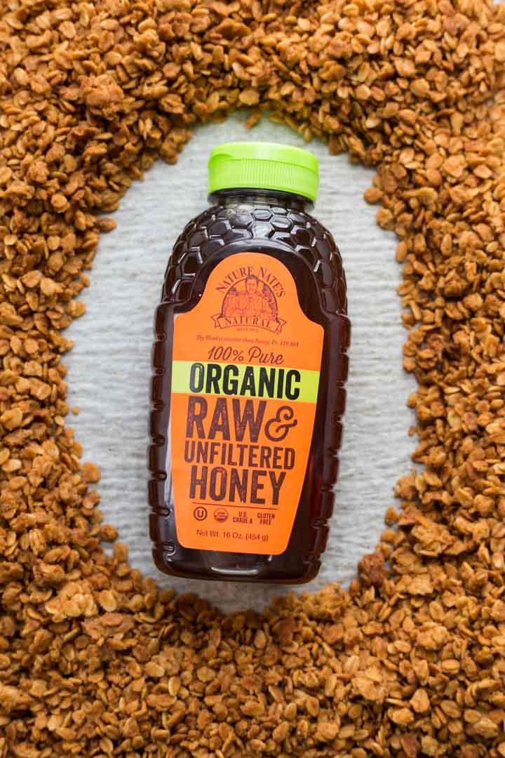 Bottle of organic Nature Nate's honey surrounded by honey granola